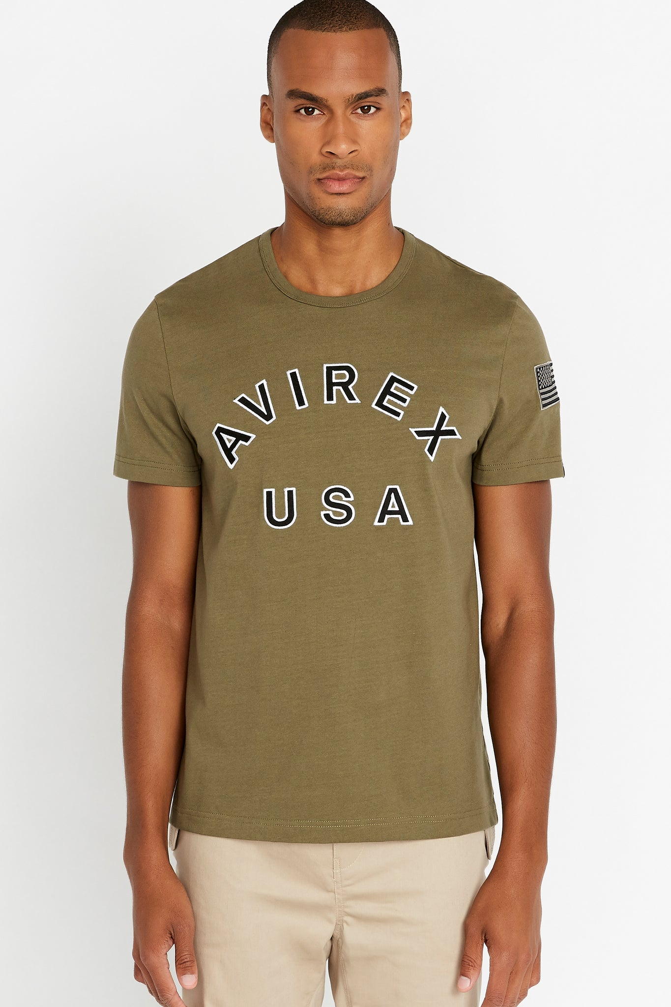 Men wearing an olive short sleeve crew T-shirt with bold logo across the front saying Avirex USA