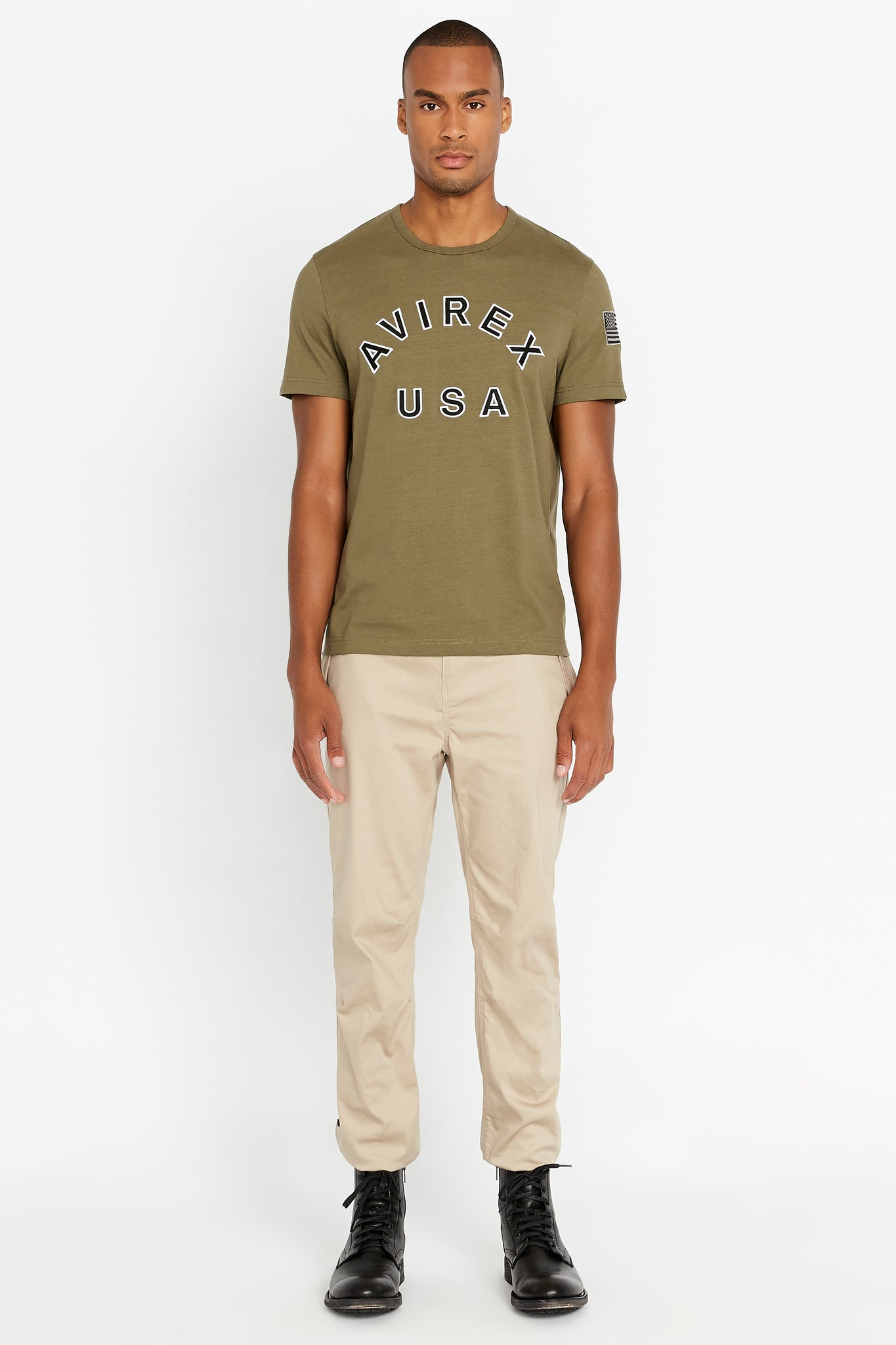 Full view of men wearing an olive short sleeve crew T-shirt with bold logo across the front saying Avirex USA and a patch on left sleeve and light beige pants