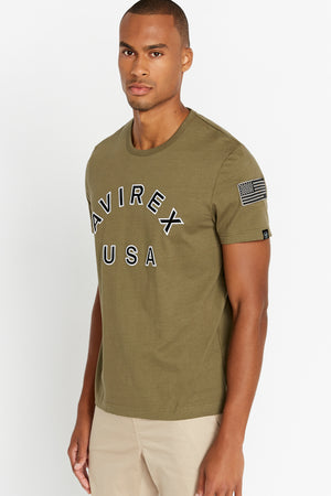Side view of men wearing an olive short sleeve crew T-shirt with bold logo across the front saying Avirex USA and a patch on left sleeve