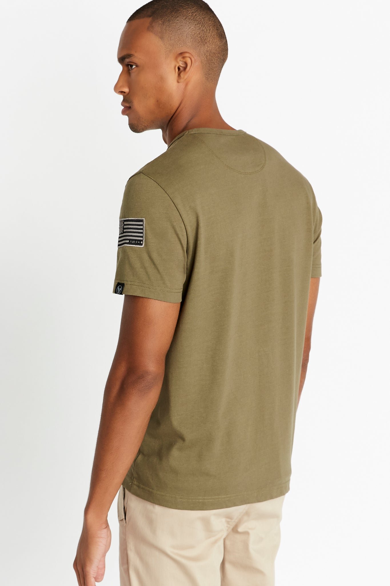 Back view of men wearing an olive short sleeve crew T-shirt with patch on left sleeve