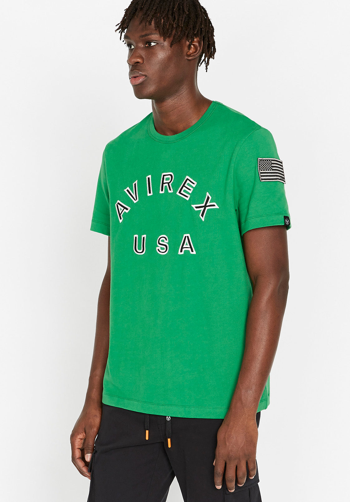 Side view of men wearing a green t-shirt with Avirex USA embroidery in black & white on front chest paired and USA flag patch on left arm