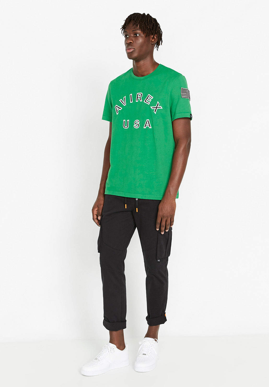 Full view of men wearing a green t-shirt with Avirex USA embroidery in black & white on front chest paired with black cargo pants