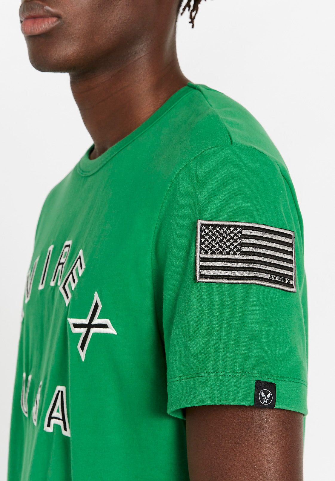 Detailed view of USA flag & Winstar embroidery patches on green t-shirt