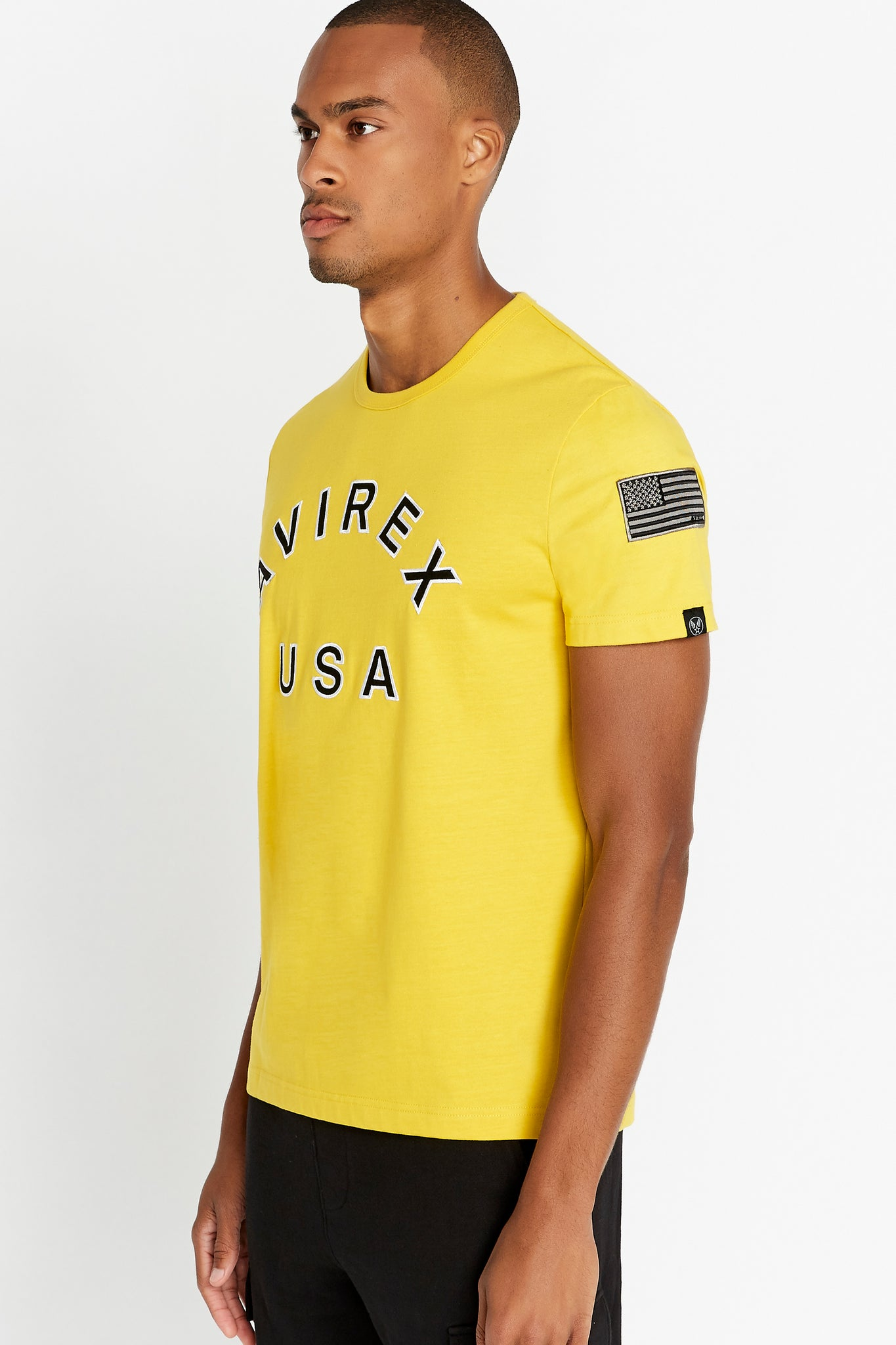 Side view of men wearing a yellow short sleeve crew T-shirt with bold logo across the front saying Avirex USA and a patch on left sleeve