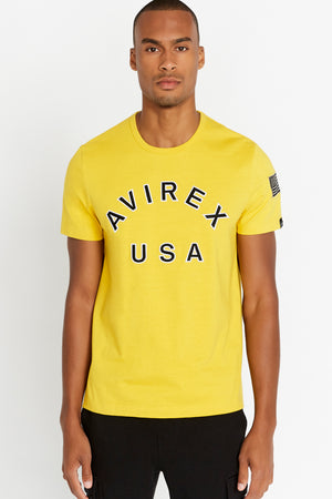 Men wearing a yellow short sleeve crew T-shirt with bold logo across the front saying Avirex USA