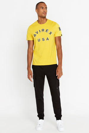 Full view of men wearing a yellow short sleeve crew T-shirt with bold logo across the front saying Avirex USA and black pants