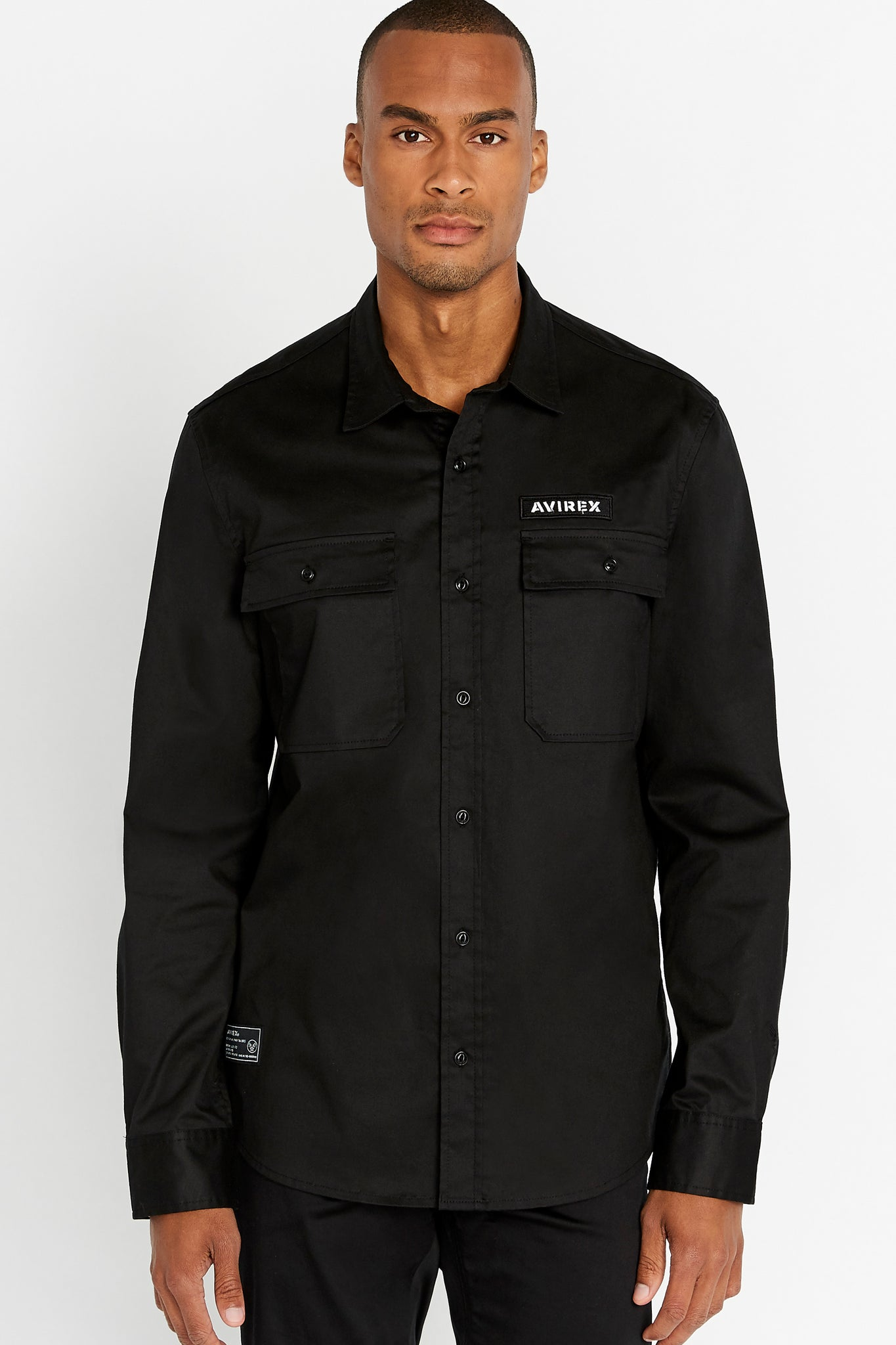 Men wearing a black long sleeve shirt with two front button-flap pockets white logo on left chest and white patch on right bottom corner
