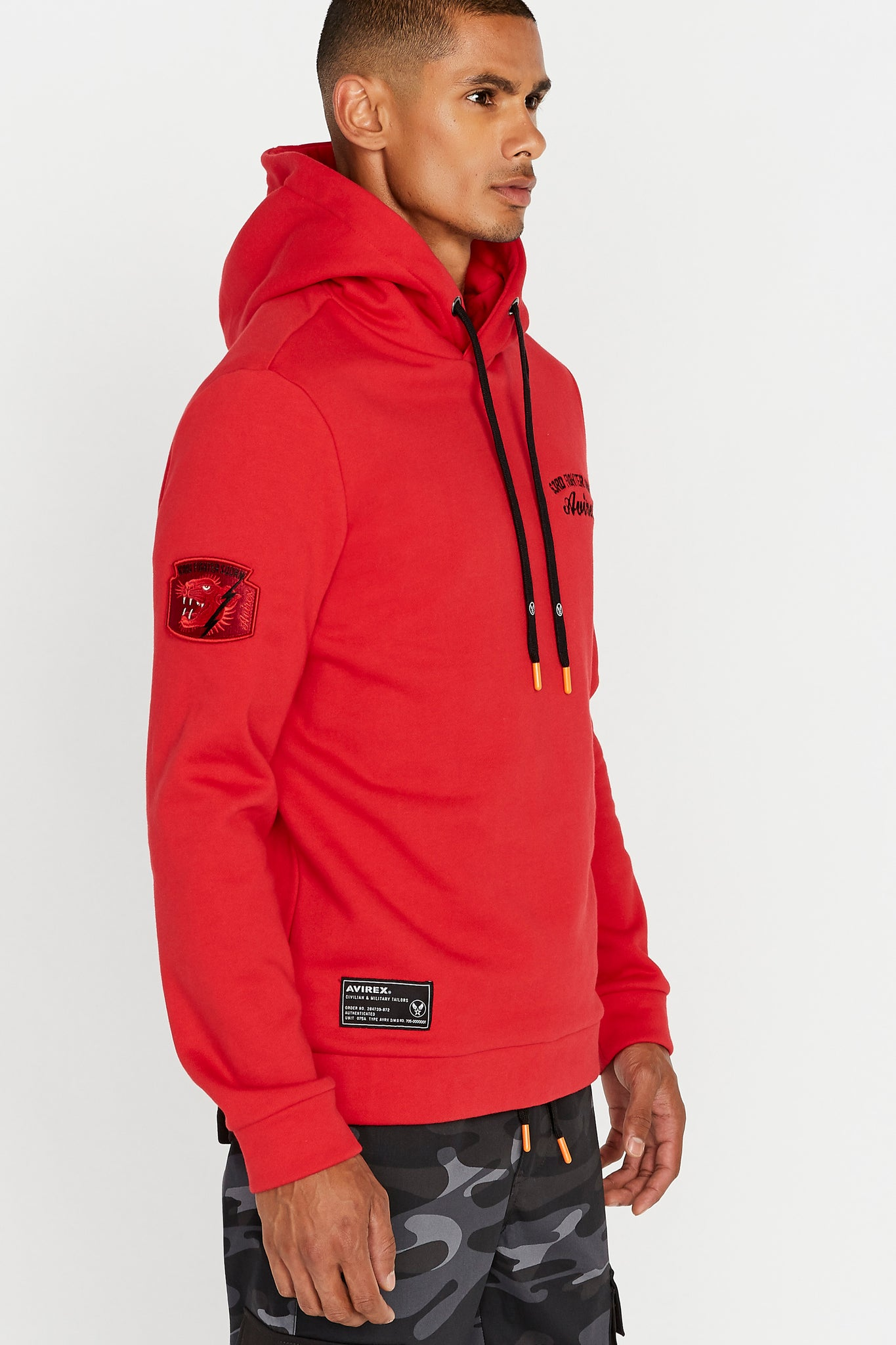 Side view of men wearing a red hoodie sweatshirt with chest embroidery and a patch on the right sleeve