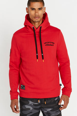 Men wearing a red hoodie sweatshirt with chest embroidery and a patch on the right sleeve