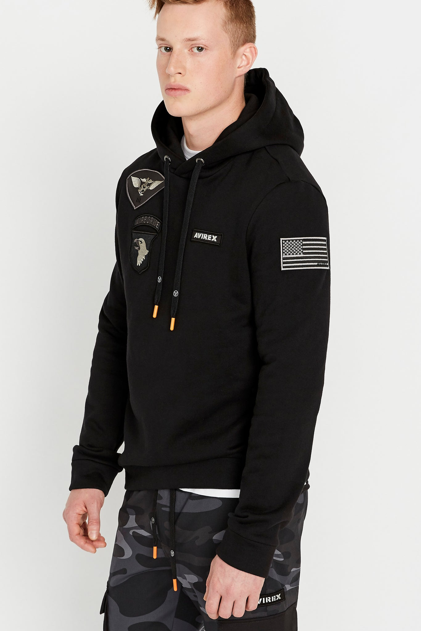Side view of man wearing a black long sleeve hoodie sweatshirt with multi-patch design on the chest and on the sleeve