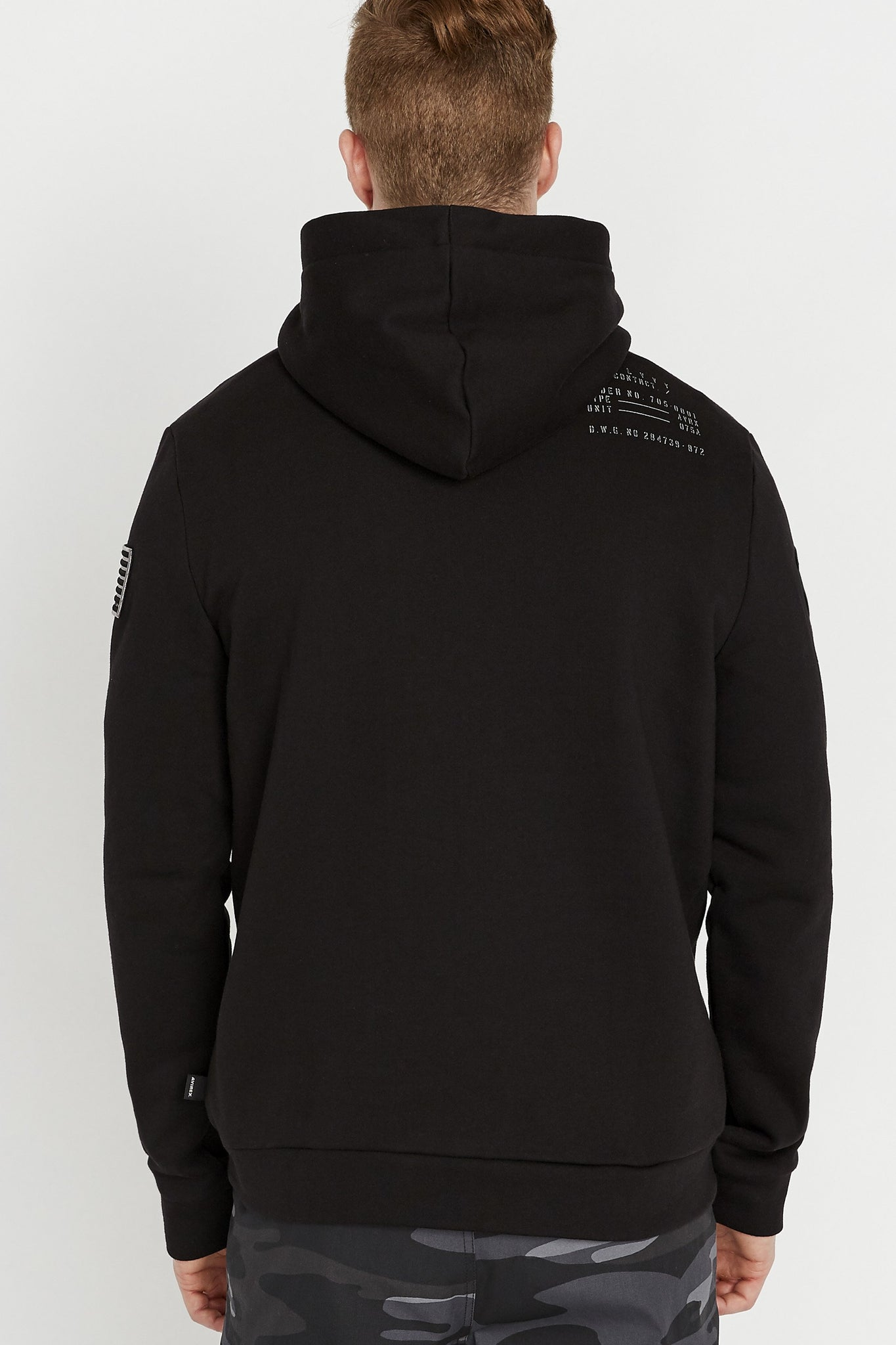 Back view of man wearing a black long sleeve hoodie sweatshirt with text print on the back shoulder