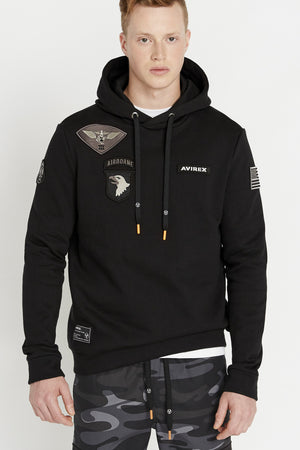 Man wearing a black long sleeve hoodie sweatshirt with multi-patch design on the chest and on the sleeve