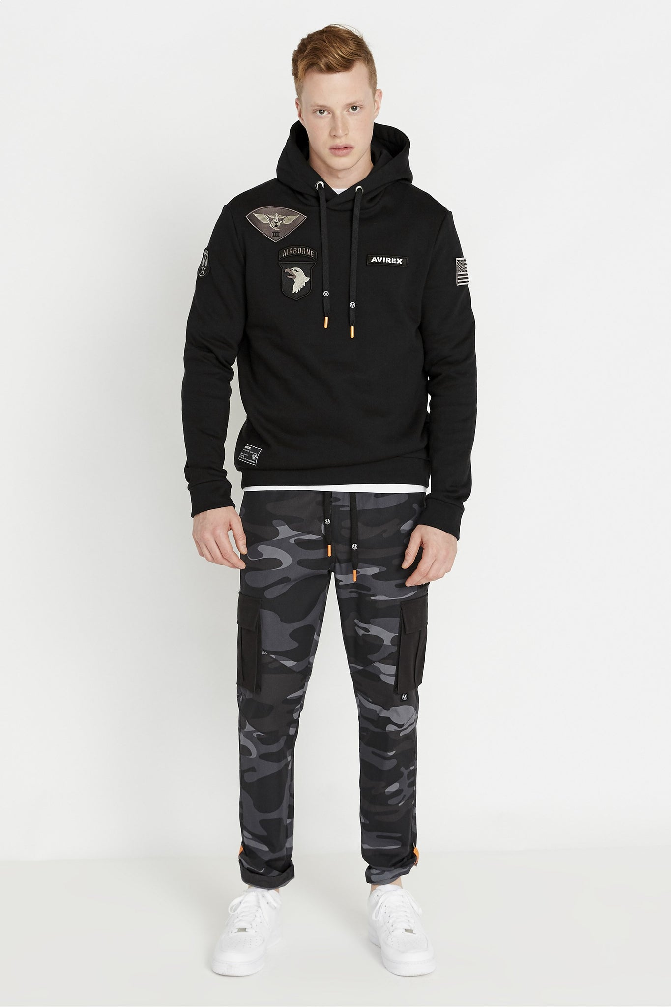 Full view of man wearing a black long sleeve hoodie sweatshirt with multi-patch design on the chest and on the sleeve and black camo print pants