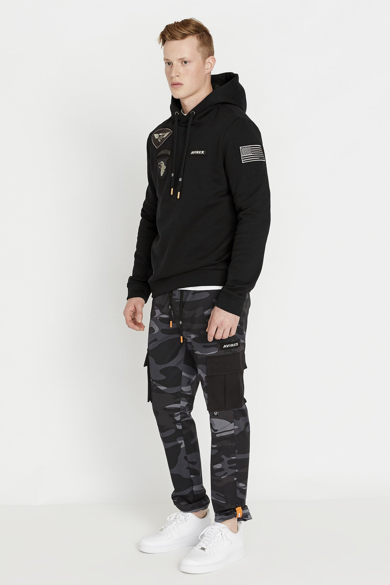 Side full view of man wearing a black long sleeve hoodie sweatshirt with multi-patch design on the chest and on the sleeve and black camo print pants