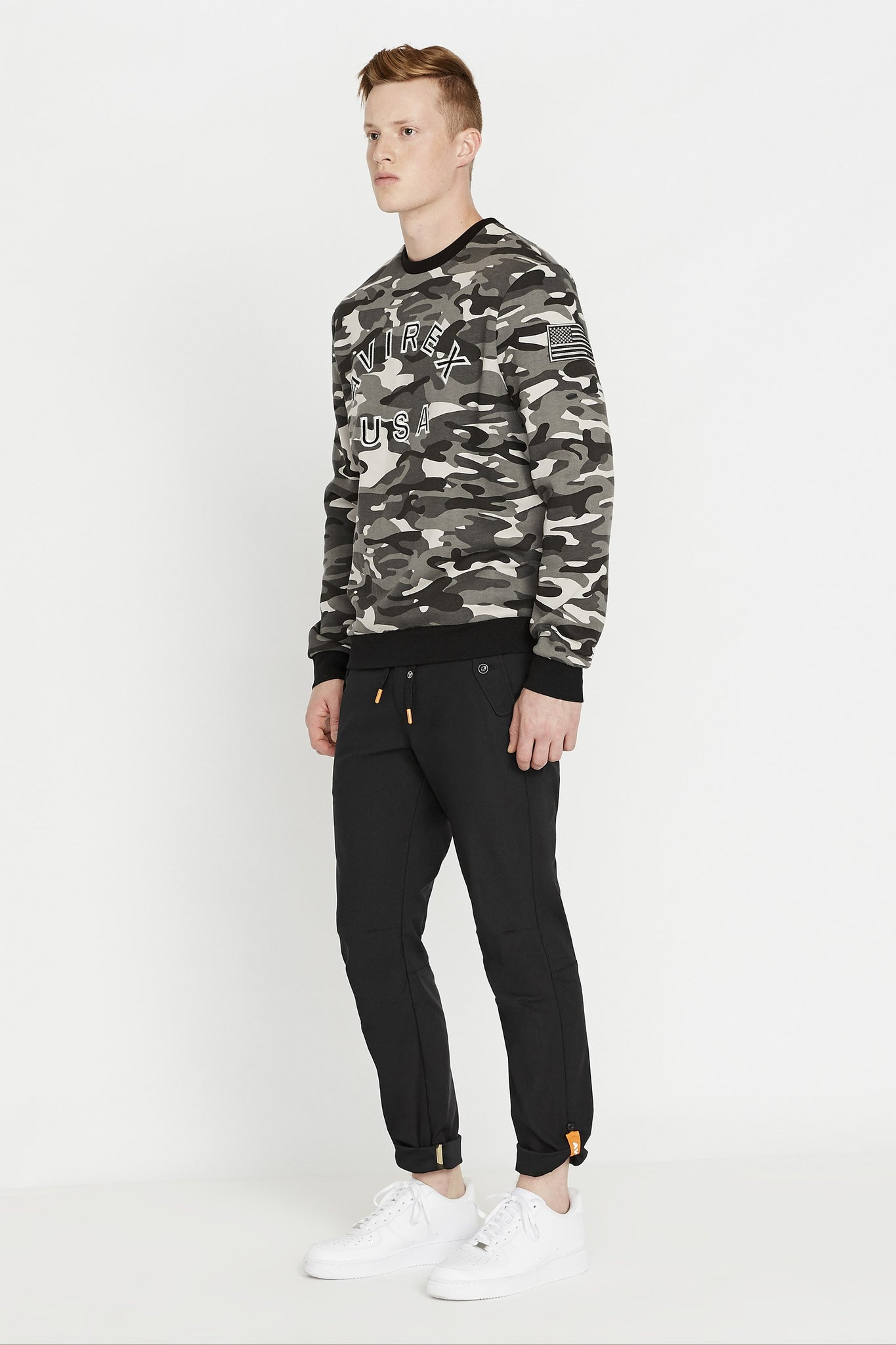 Side full view of men wearing a black camo long sleeve crew neck sweater with bold front embroidered logo and a patch on the left sleeve and black pants
