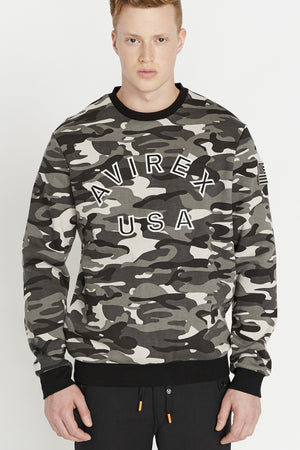 Men wearing a black camo long sleeve crew neck sweater with bold front embroidered logo and a patch on the left sleeve