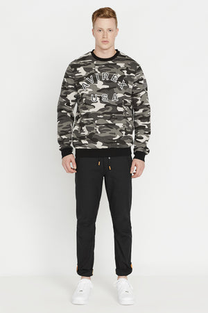 Full view of men wearing a black camo long sleeve crew neck sweater with bold front embroidered logo and a patch on the left sleeve and black pants