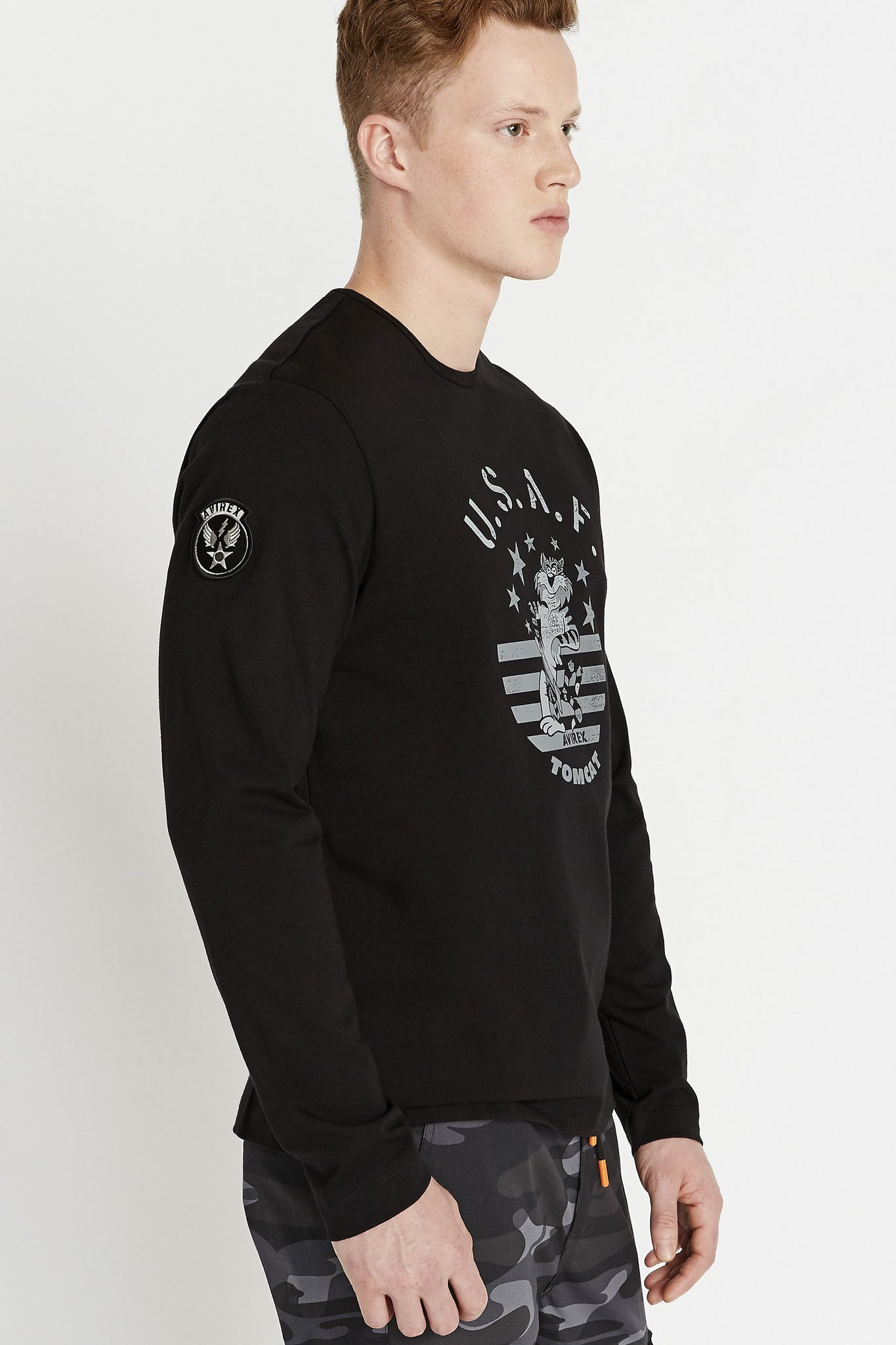 Side view of men wearing a black long sleeve crew T-shirt with front Tomcat graphics and a patch on the right sleeve