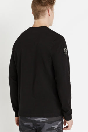 Back view of men wearing a black long sleeve crew T-shirt and a patch on the right sleeve