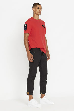 Side view of men wearing a red short sleeve crew T-shirt with contrast Avirex logo and letters patch on left chest and a patch on right sleeve and black pants