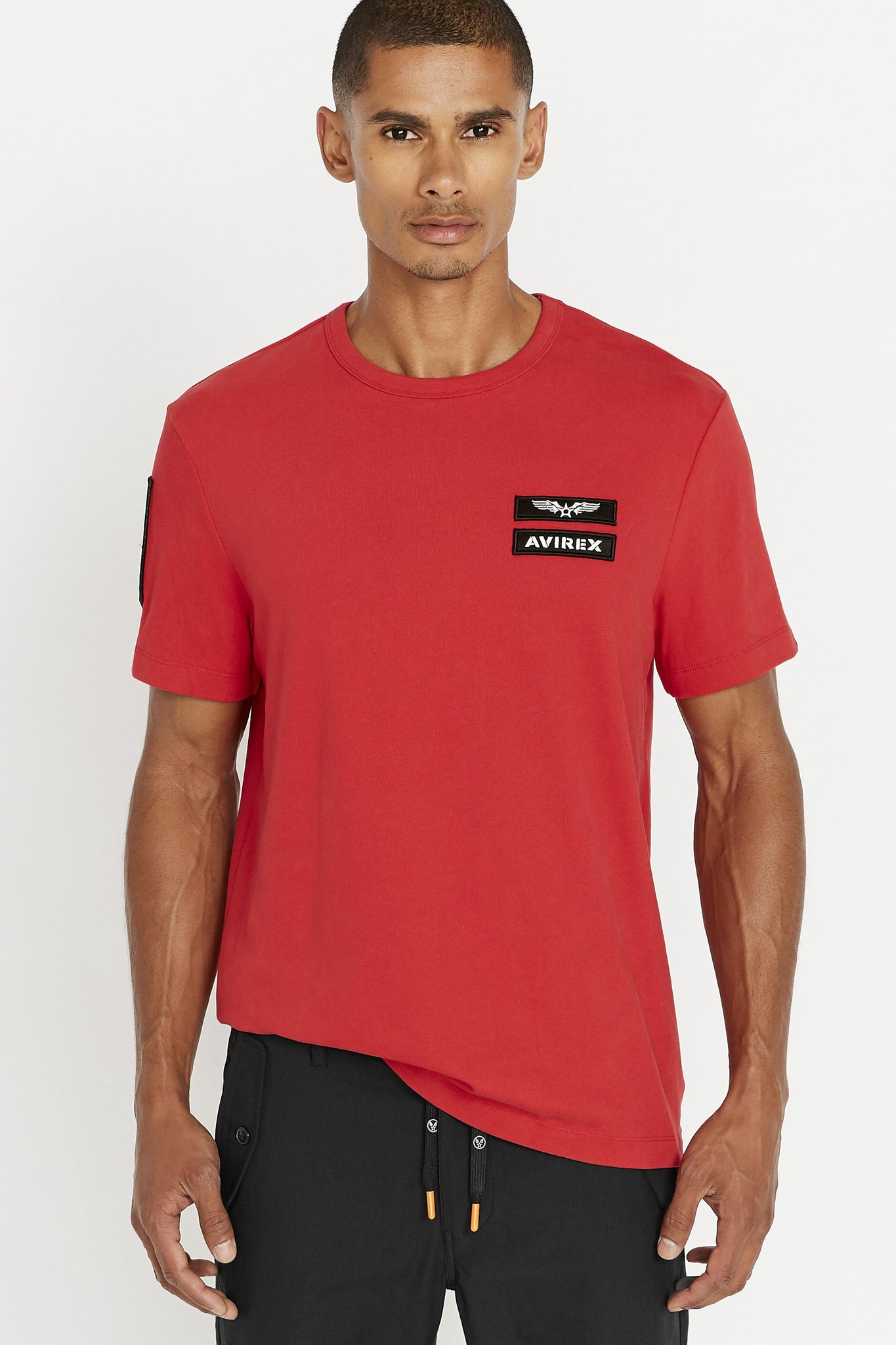 Men wearing a red short sleeve crew T-shirt with contrast Avirex logo and letters patches on left chest and a patch on right sleeve