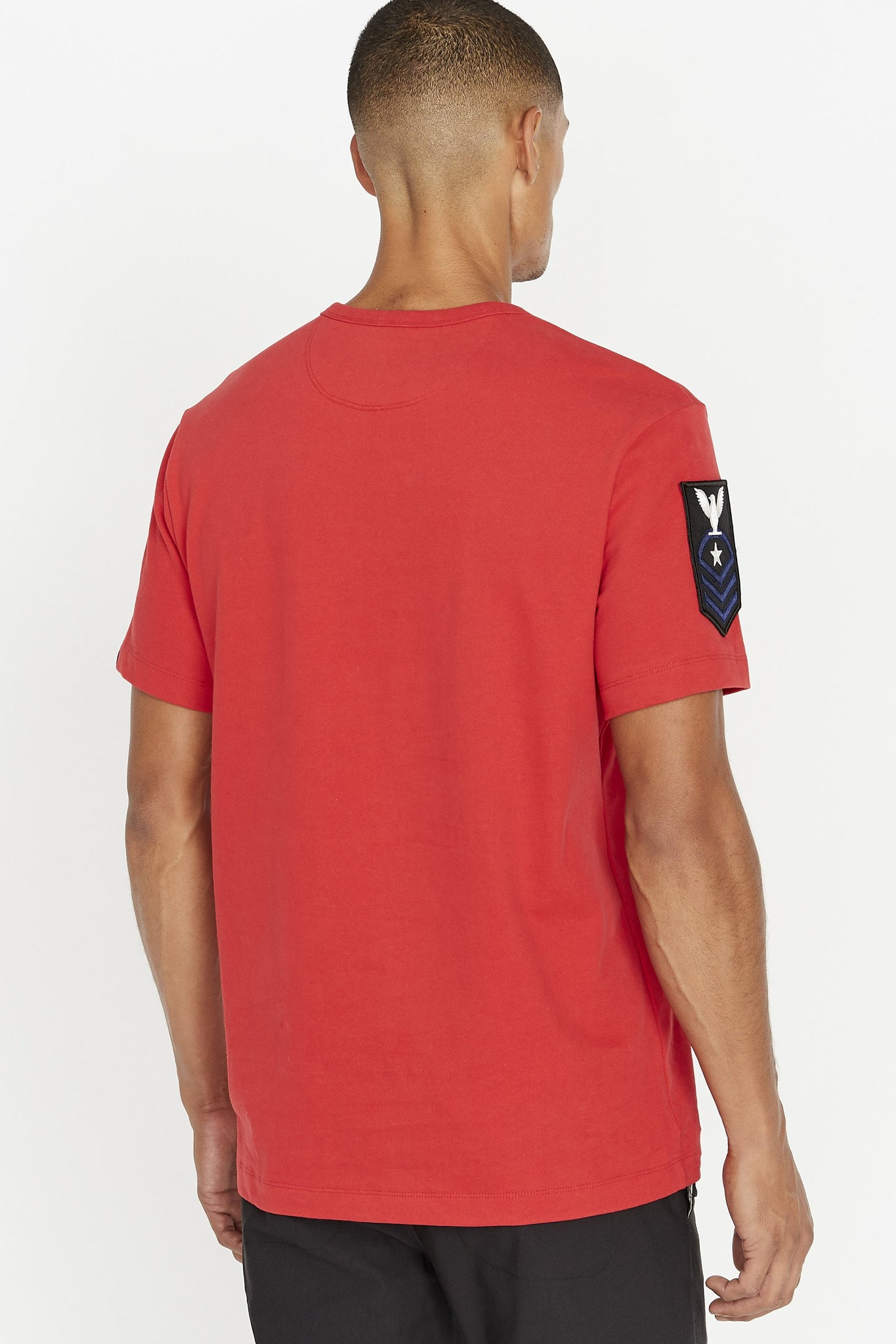 Back view of men wearing a red short sleeve crew T-shirt with contrast patch on right sleeve