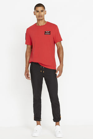 Full view of men wearing a red short sleeve crew T-shirt with contrast Avirex logo and letters patch on left chest and a patch on right sleeve and black pants