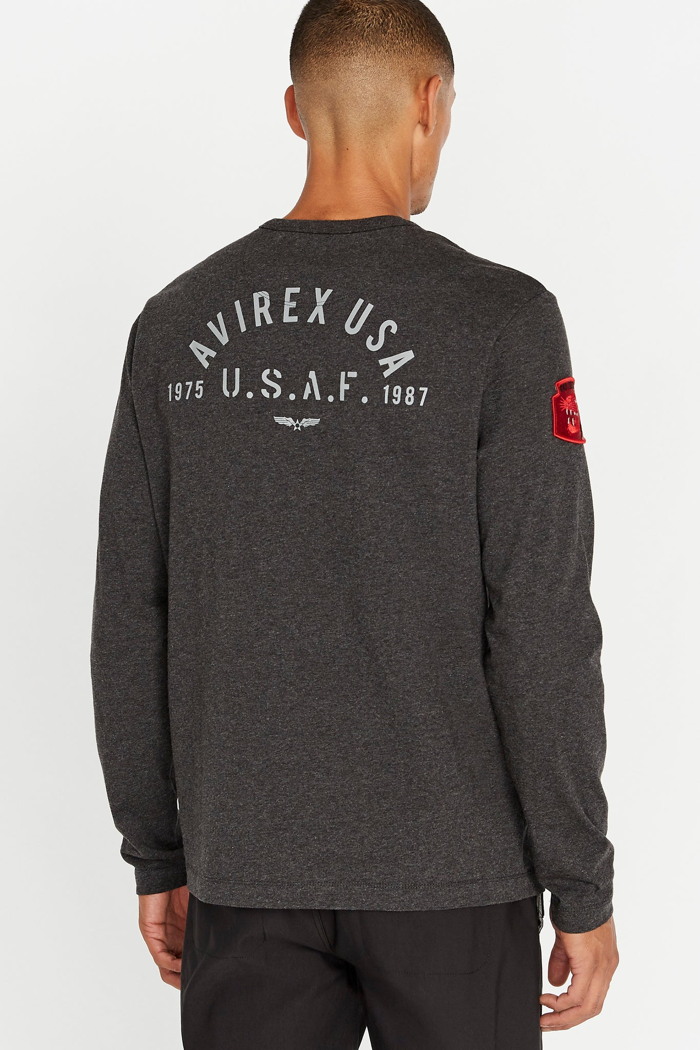 Back view of men wearing a charcoal long sleeve crew neck T-shirt with white letters saying Avirex USA