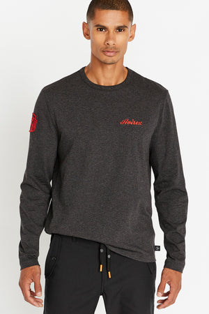Men wearing a charcoal long sleeve crew neck T-shirt with red Avirex embroidery on left chest and a red patch on right sleeve