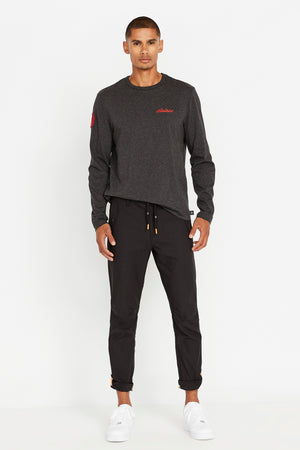 Full view of men wearing a charcoal long sleeve crew neck T-shirt with red Avirex embroidery on left chest and a red patch on right sleeve and black pants