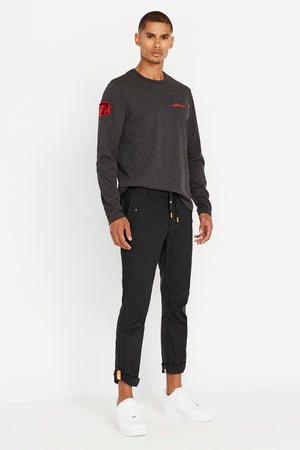 Side view of men wearing a charcoal long sleeve crew neck T-shirt with red Avirex embroidery on left chest and a red patch on right sleeve and black pants