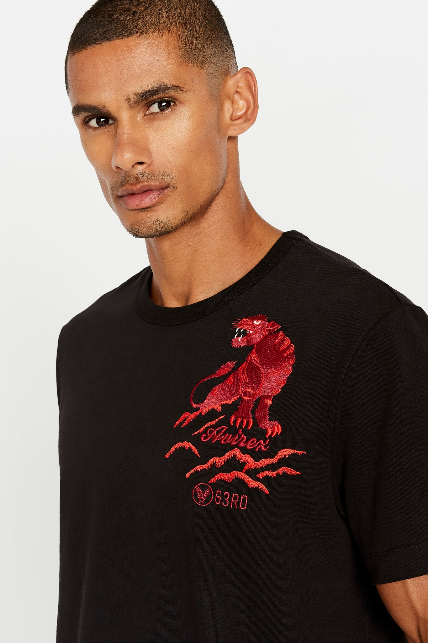 Detailed view of red panther embroidery on left chest