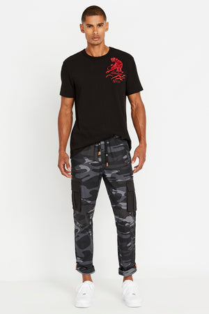 Full view of men wearing a black short sleeve crew neck T-shirt with red panther embroidery on left chest and dark grey camo print pants