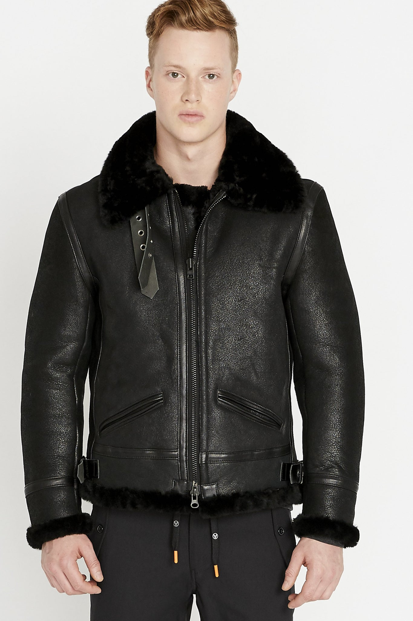 Front view of men wearing a fully zipped black sheepskin jacket with shearling fur lined collar sleeves and waist with two pockets