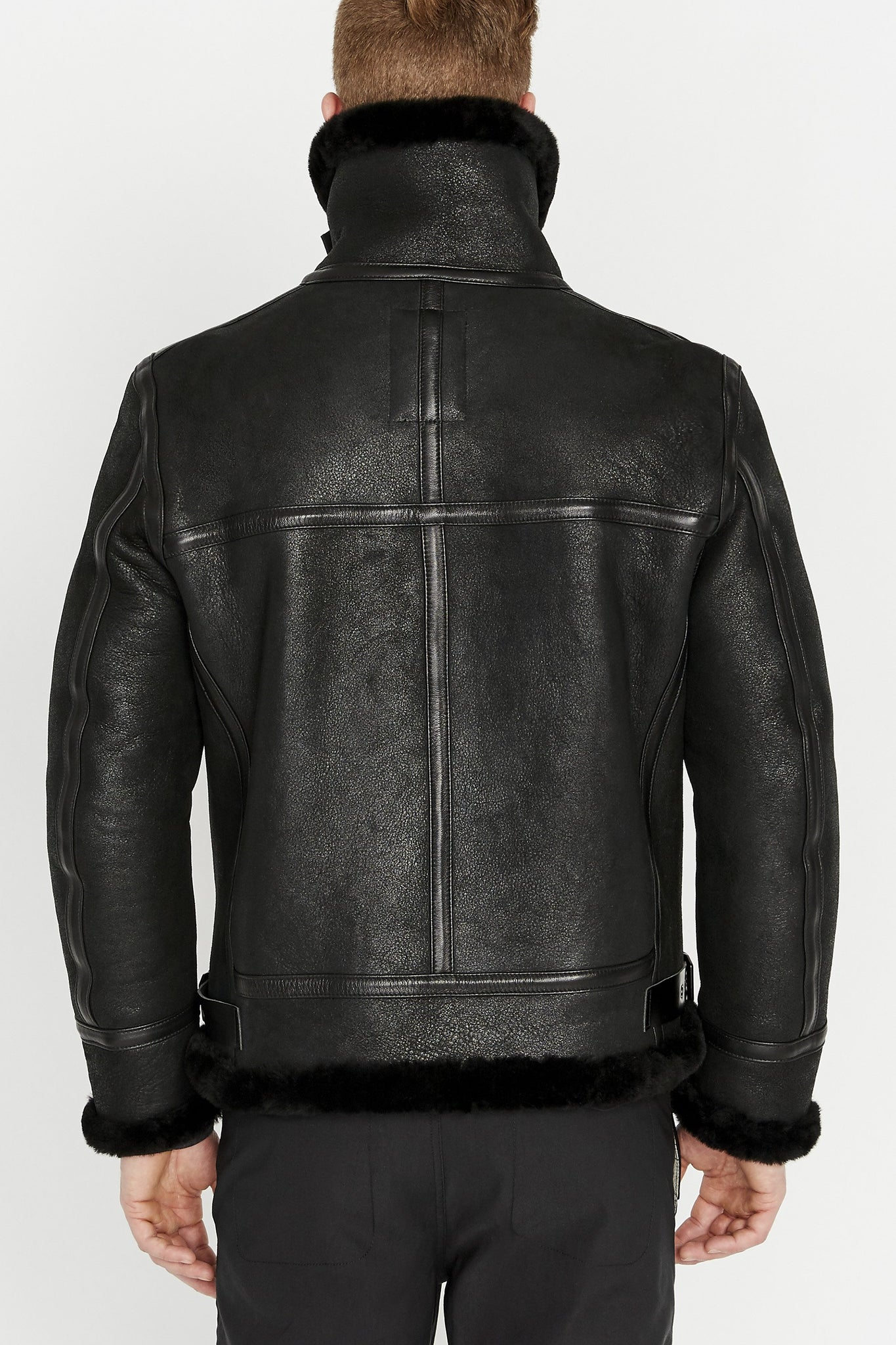 Back view of men wearing black sheepskin jacket with shearling fur lined collar sleeves and waist