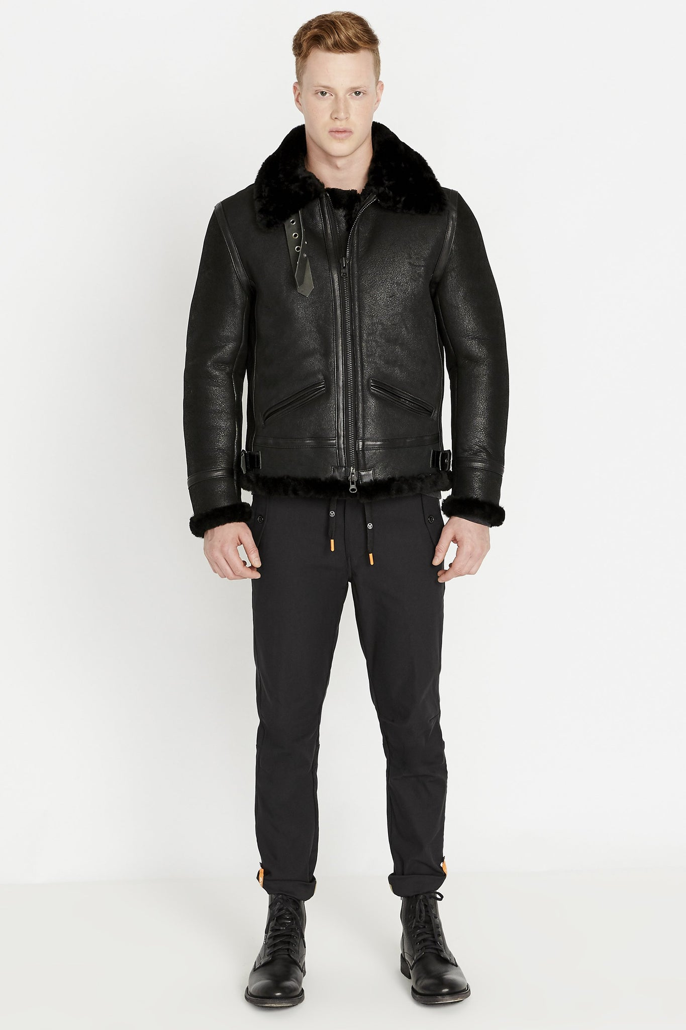 Front full view of men wearing a fully zipped black sheepskin jacket with shearling fur lined collar sleeves and waist with two pocket and black pants