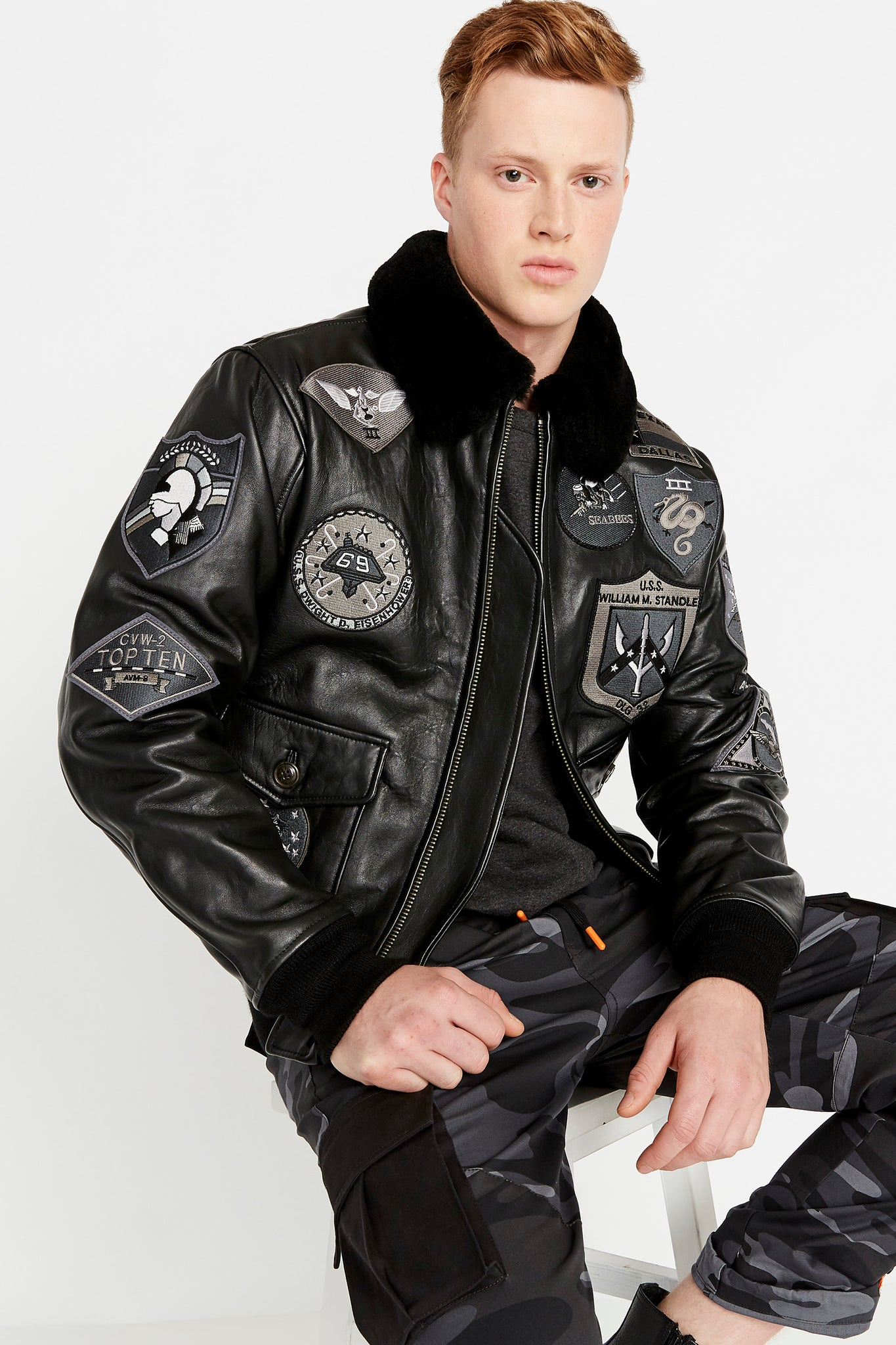 Men sitting wearing Top Gun G-1 leather jacket with shearling fur lined collar and blackout Top gun patch design on bodice.