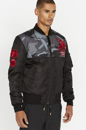 Side view of men wearing a fully zipped black bomber jacket with camo print on the chest and red embroidery panther on the left chest, two red patches on right sleeve and two side flap pockets on the sides