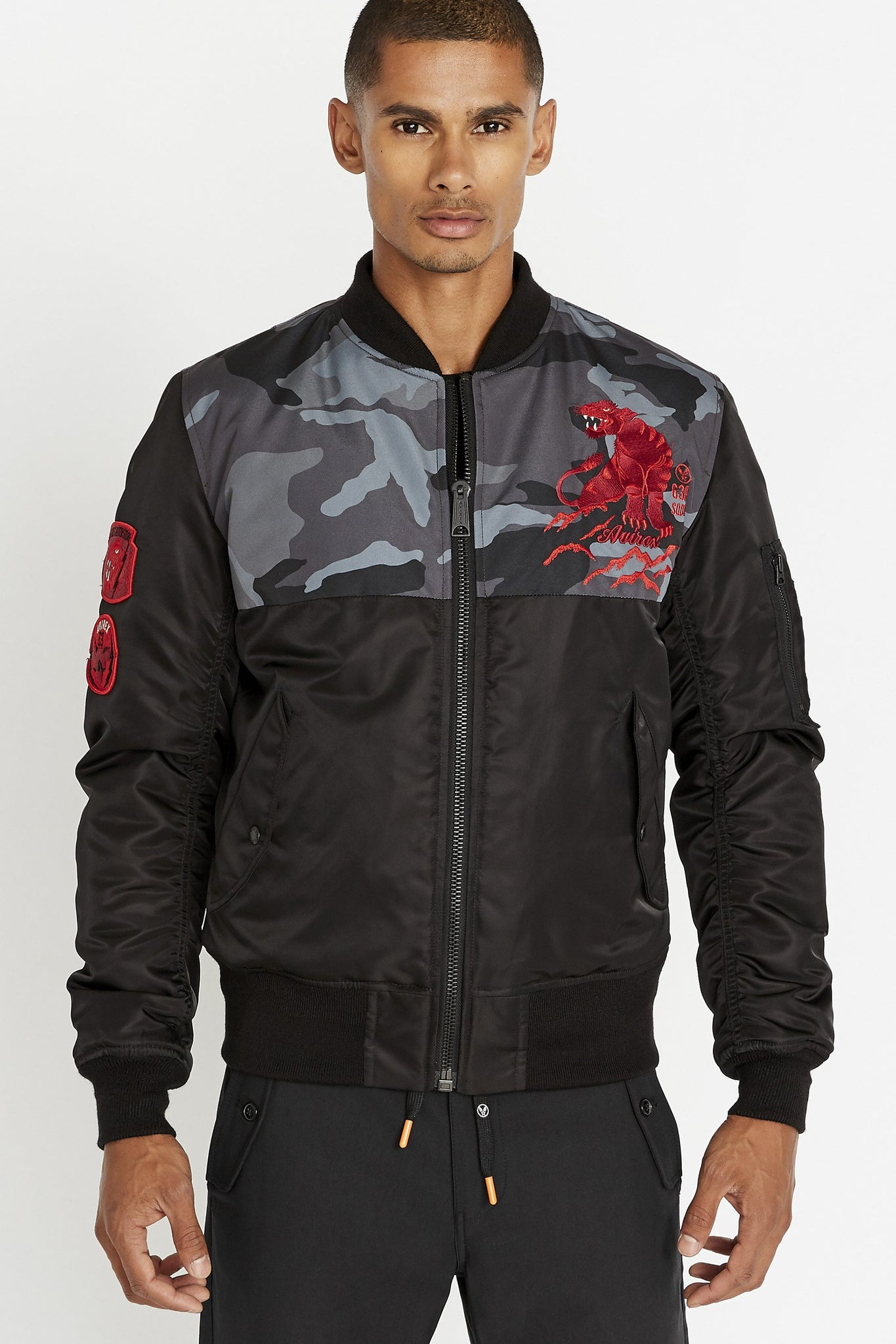Front view of men wearing a fully zipped black bomber jacket with camo print on the chest and embroidery red panther on the left chest and two side flap pockets on the sides
