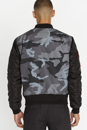 Back view of men wearing a black bomber jacket with camo printed allover back