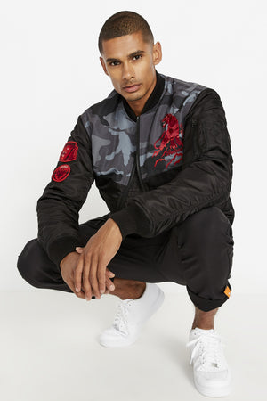 Front view of a crouching men weaing an open black bomber jacket with camo print on the chest and embroidery red panther on the left chest and black pants