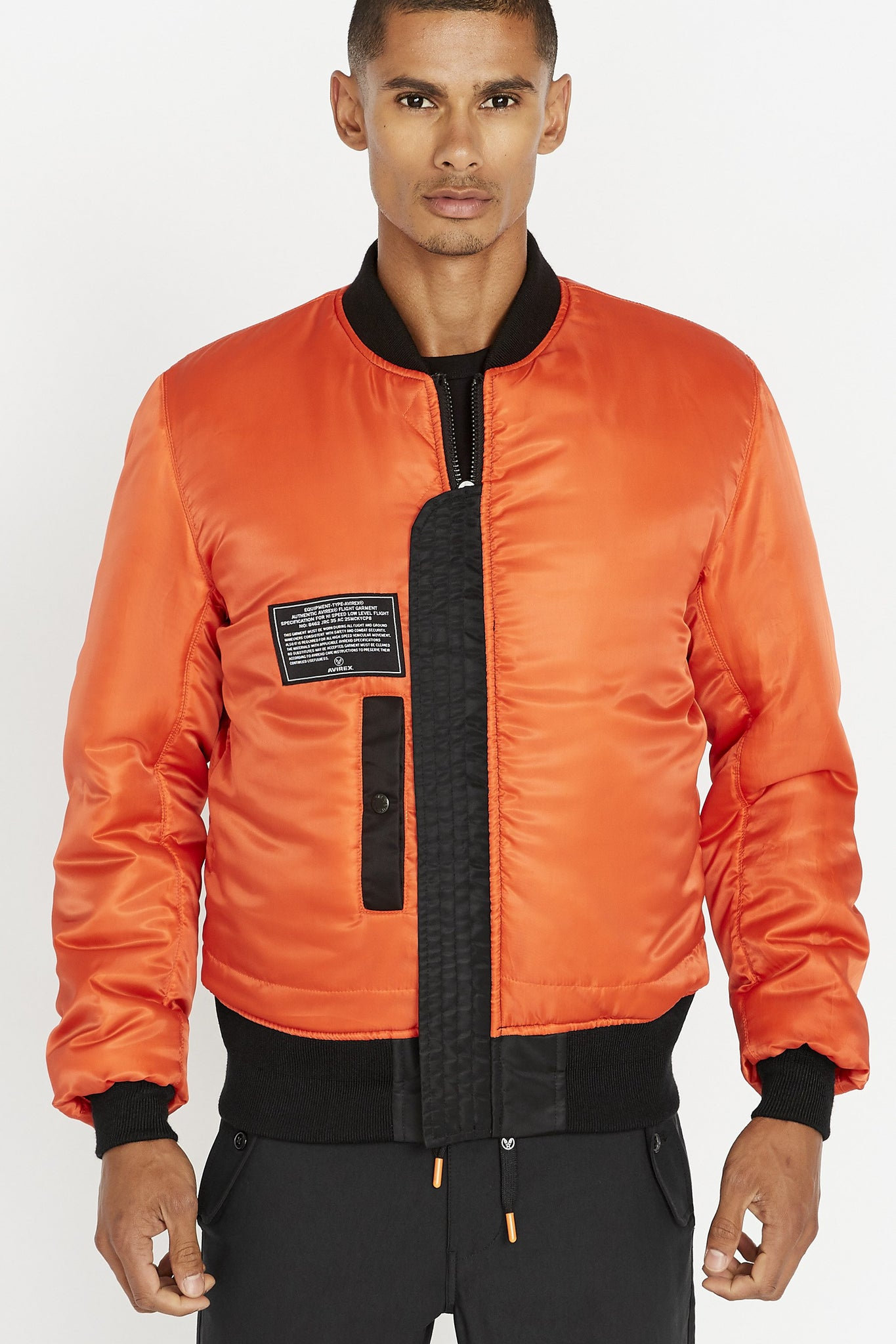Front view of men wearing a fully zipped reversed orange bomber jacket with one patch and one pocket on the right chest