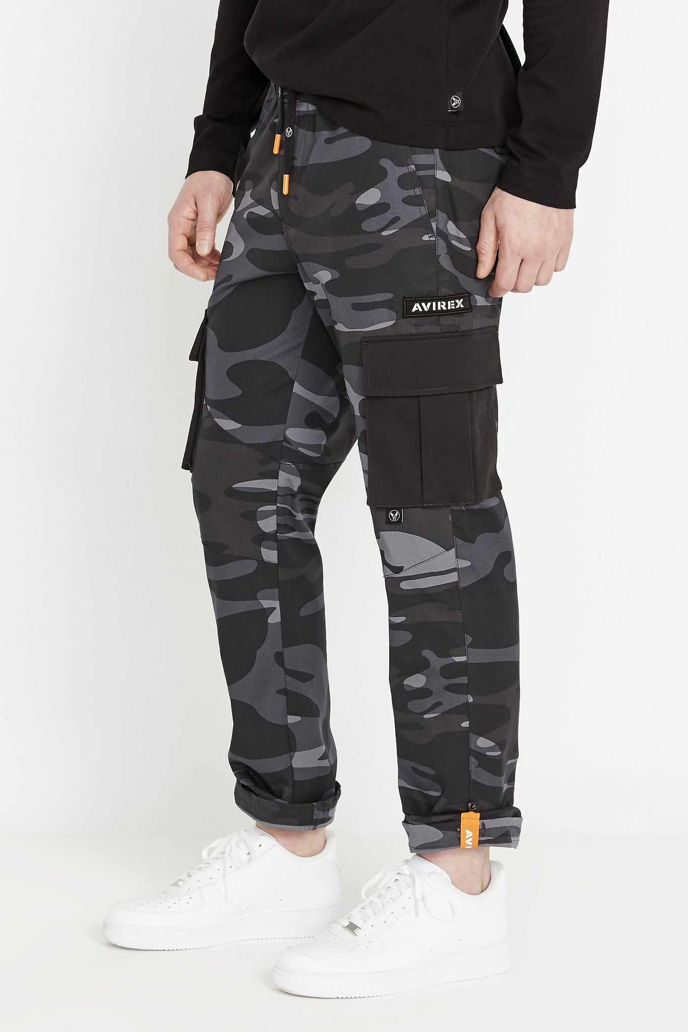 Side view of black camo print pants with cargo pockets in solid color and Avirex Patch above.  Rolled up hem with reflective logo