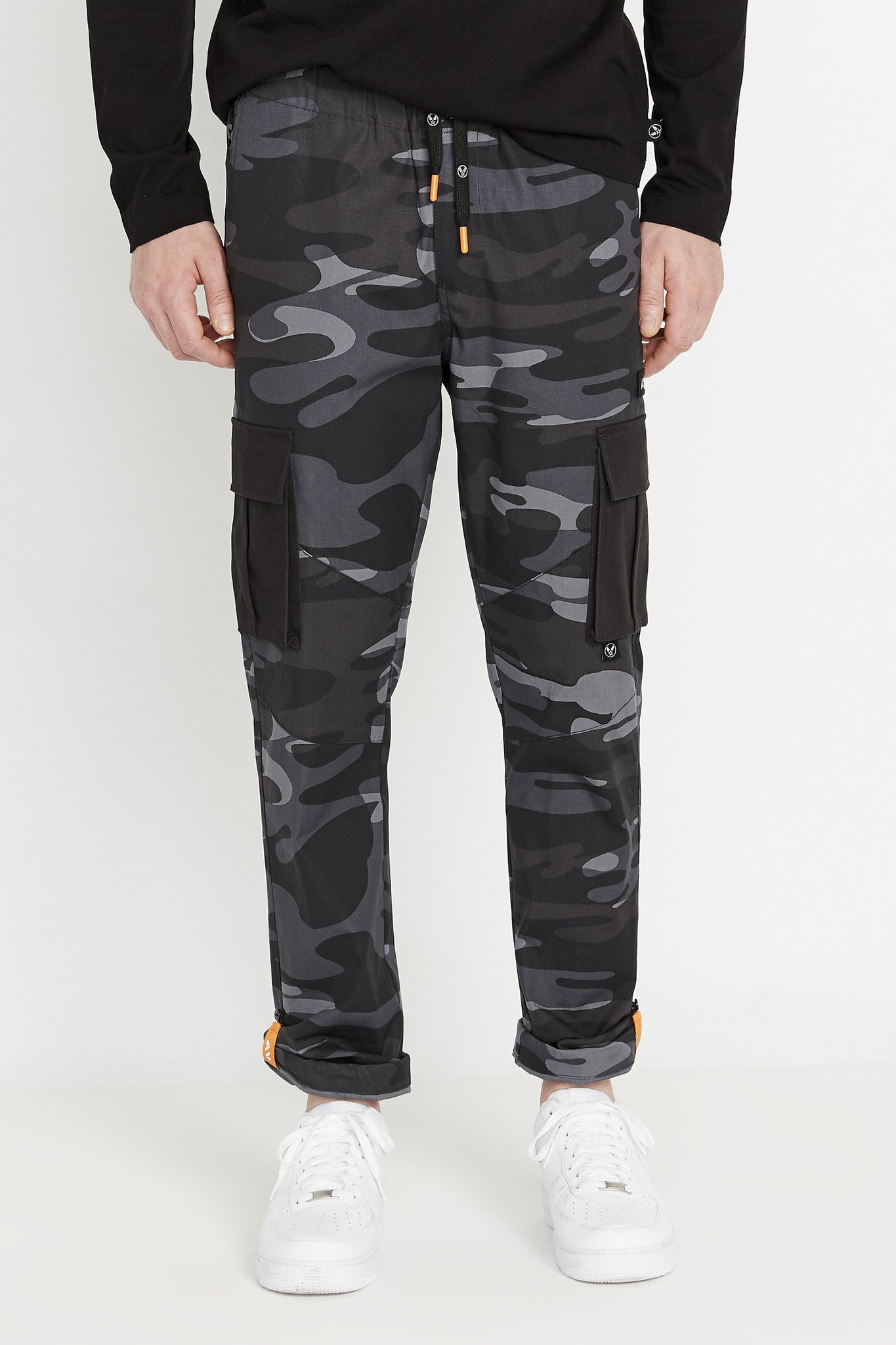 Front view of black camo print pants with side cargo pockets in solid color.  Rolled up hem with reflective logo