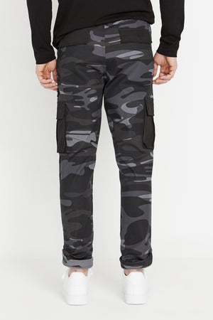 Back view of black camo print pants with flap and side cargo pockets in solid color.  Rolled up hem with reflective logo