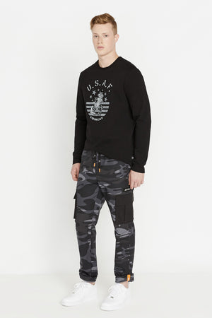 Full side view of men wearing black camo print pants with cargo pockets in solid color.  Rolled up hem with reflective logo