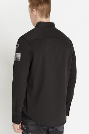 Back view of men wearing a black long sleeve shirt with two buttons on each sleeve