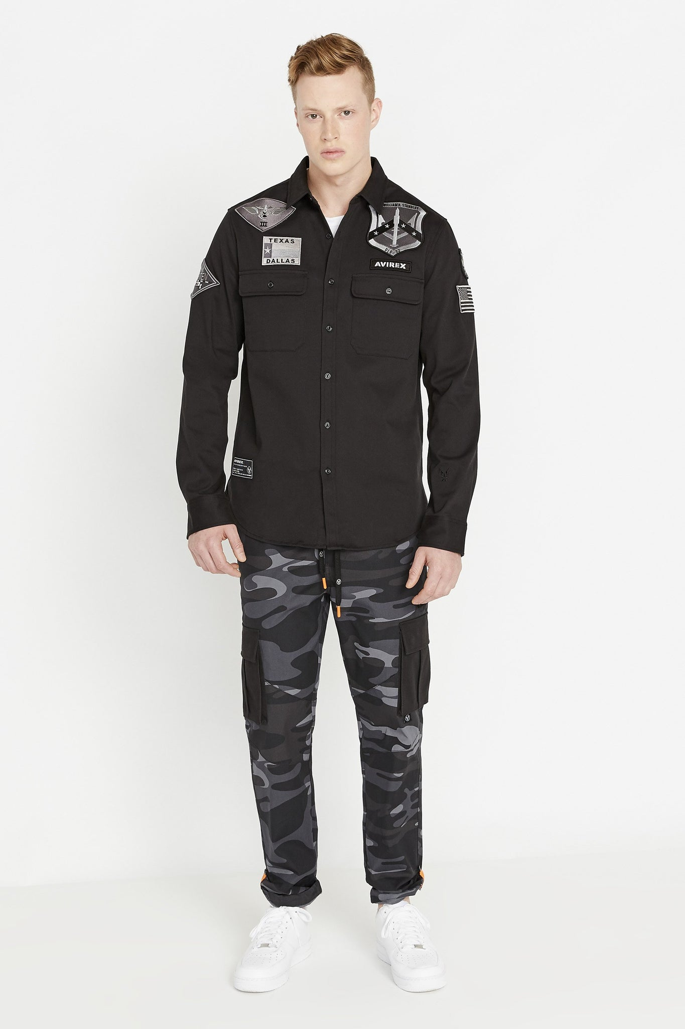 Full view of men wearing a black long sleeve shirt with two front button-flap pockets multi-patch on the chest and arms and black camo print pants