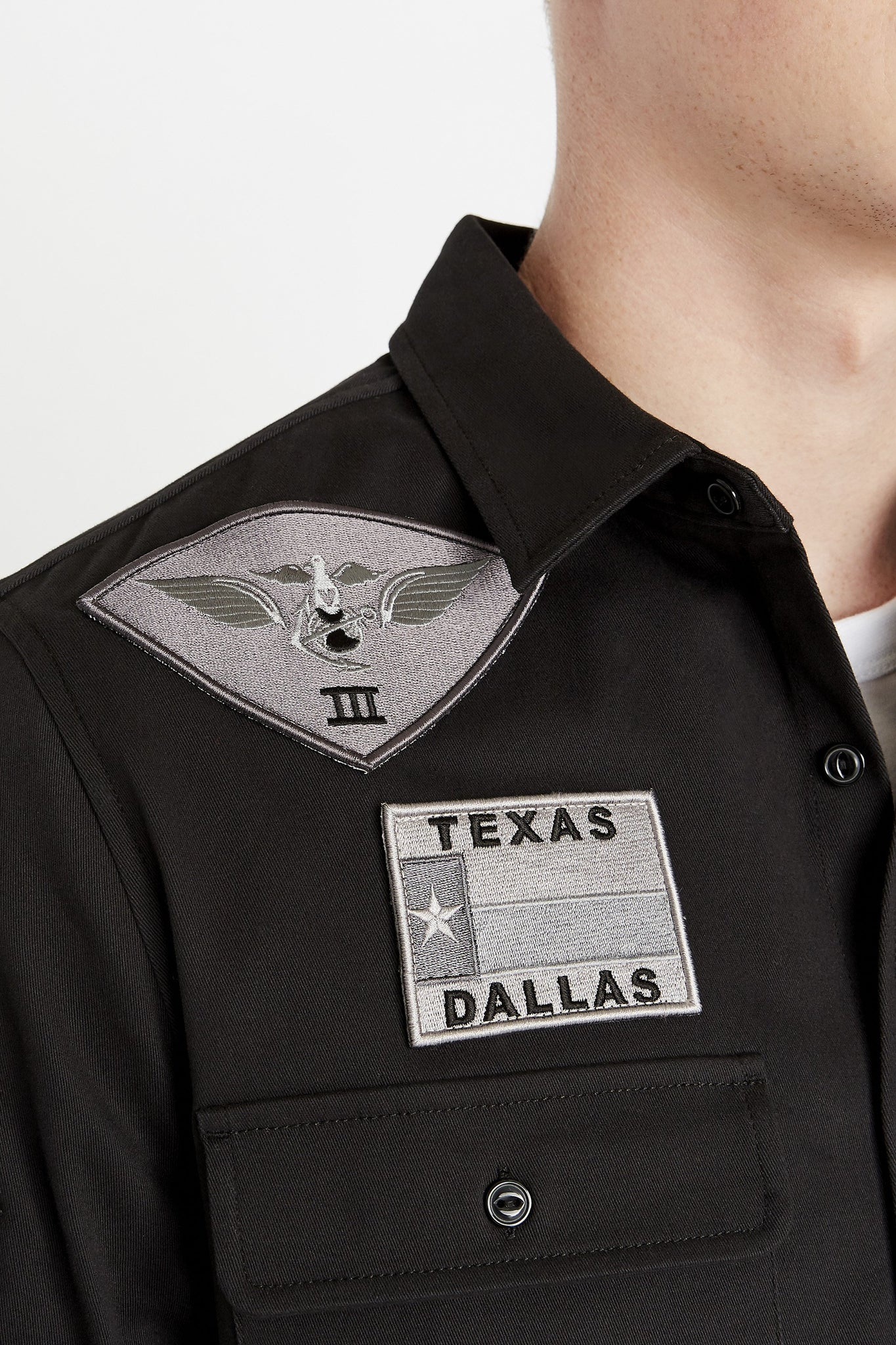 Detailed view of embroidery logo and patch above pocket on right chest