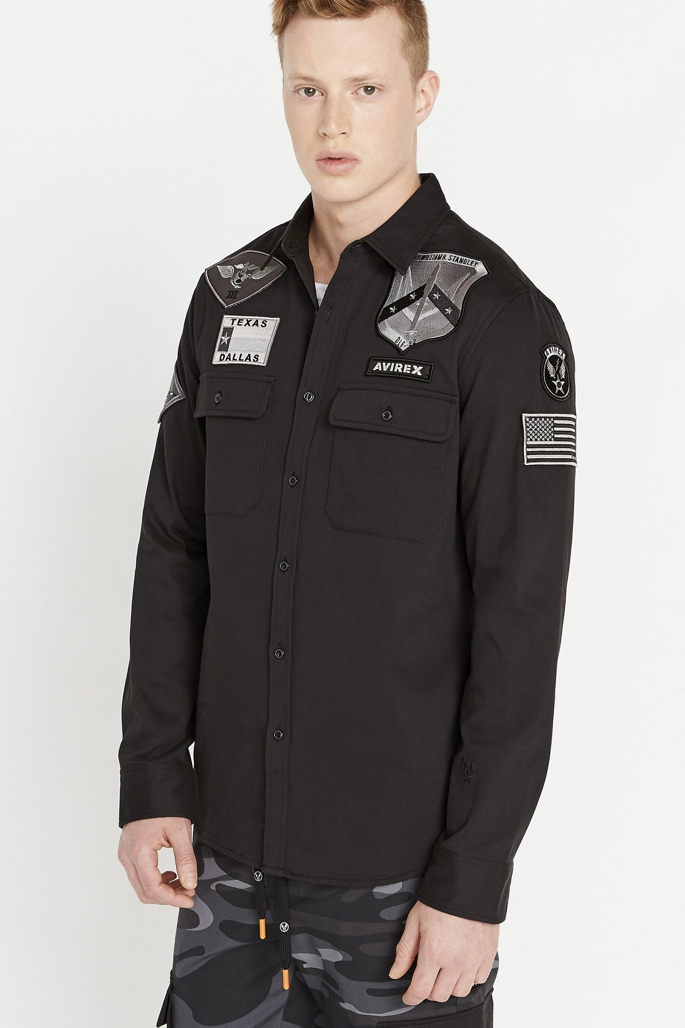 Side view of men wearing a black long sleeve shirt with two front button-flap pockets multi-patch on the chest and arms